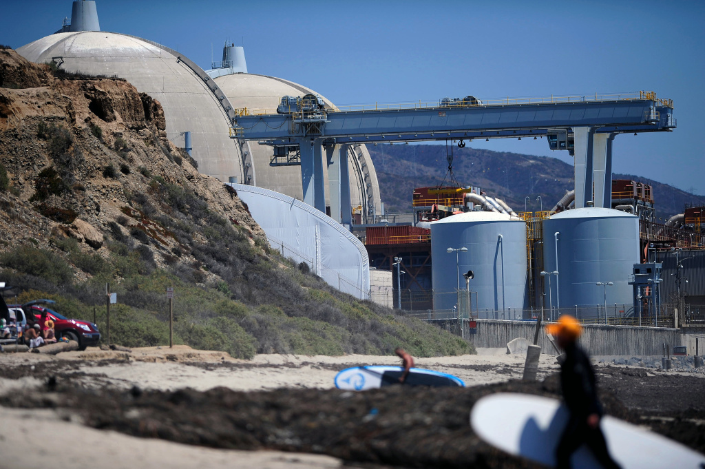 In this July 19, 2012 file photo, surfers walk along a beach nearby the San Onofre Nuclear Power Plant in San Onofre, Calif. Southern California Edison says it will challenge a proposal to refund money to customers who were charged operating costs for the now-closed plant.