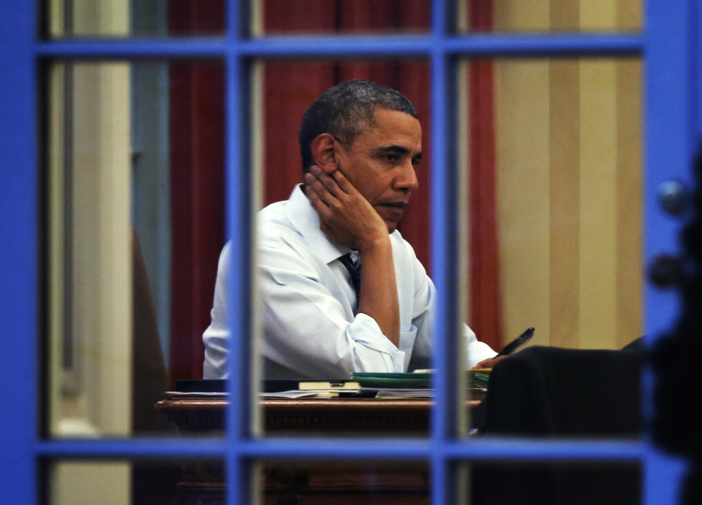 U.S. President Barack Obama sits at his desk in the Oval Office January 27, 2014 at the White House in Washington, DC. Obama will deliver his State of the Union address to a joint session of Congress at the Capitol on the night of January 28.