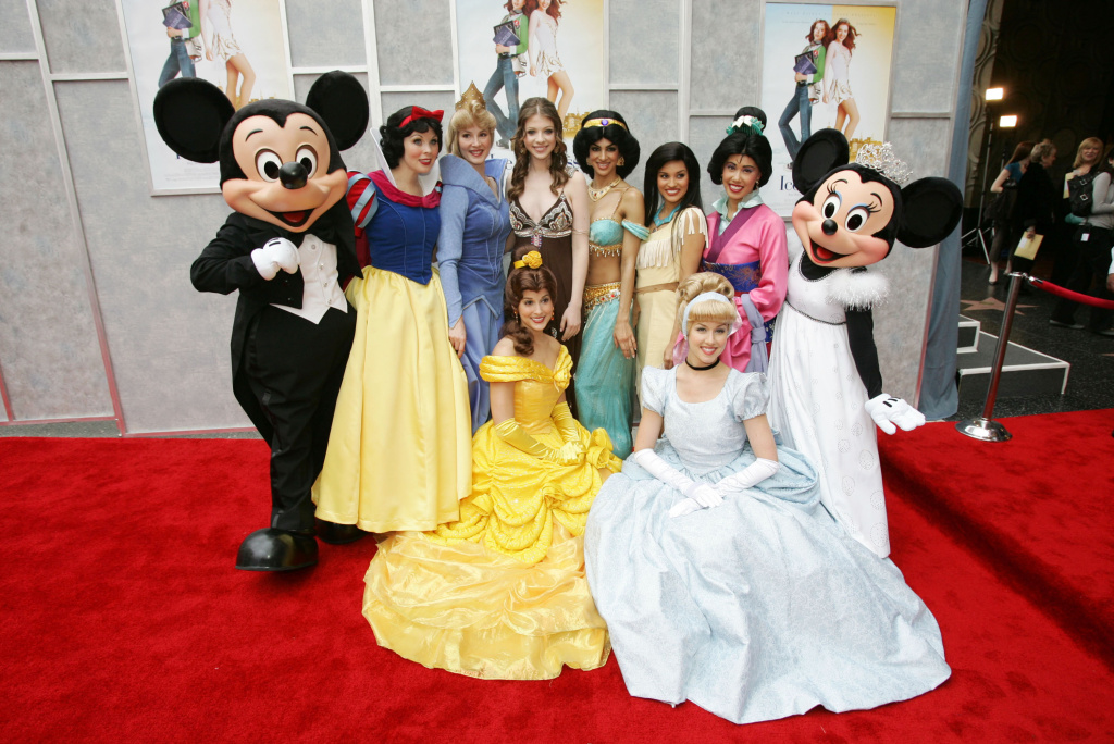 Actress Michelle Trachtenberg (centre) poses with Disney characters at the Walt Disney premiere of
