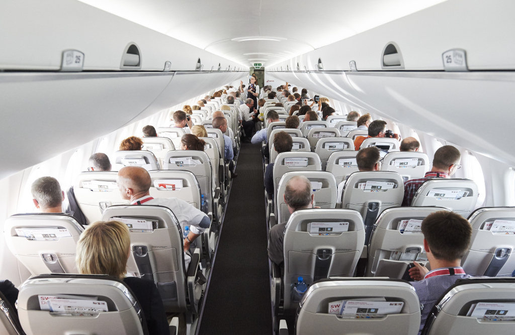 Passengers sit on July 6, 2016 aboard the Swiss International Air Lines' new Bombardier CS 100 passenger jetliner during a flight over the Swiss Alps.