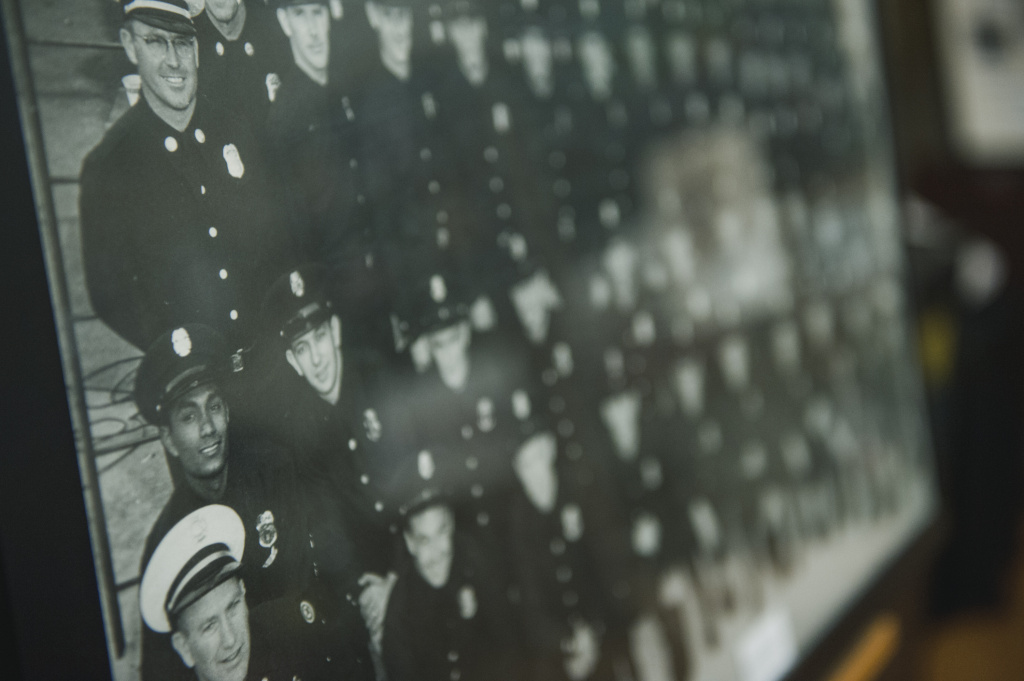 Paul Orduna, left, the first black firefighter to join the city's department in 1957, after it was integrated, is shown amongst a sea of white faces in a photo of his recruit class displayed at the African American Firefighter Museum in Los Angeles, California.