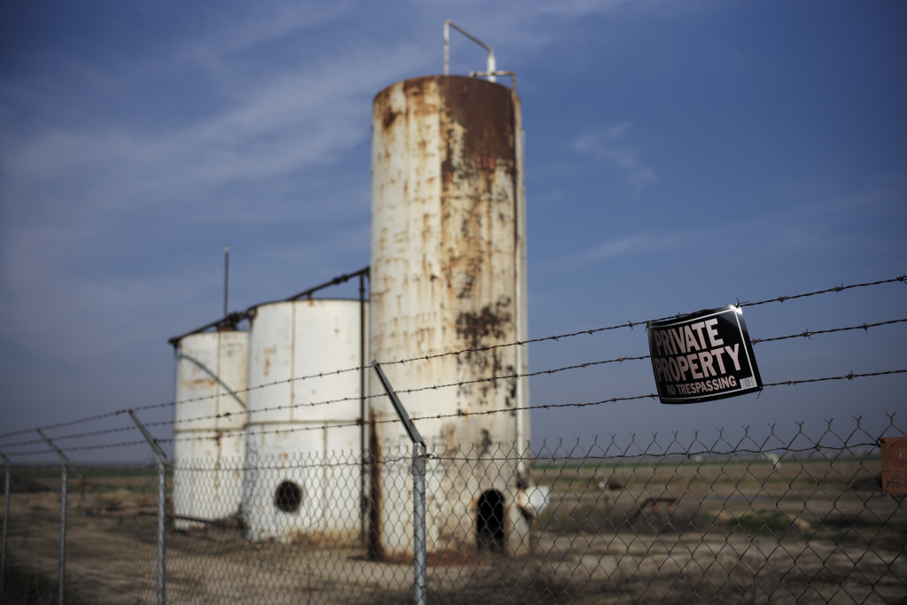 A private property sign hangs on the fence of a shut down injection well located next to an almond orchard owned by Palla Farms, Thursday, Jan. 15, 2015, in Bakersfield, Calif. Palla Farms filed suite blaming several oil companies for contaminating the local groundwater and killing cherry trees. (AP Photo/Jae C. Hong)