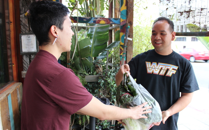 Kyle Tsukahira of the Roots C.S.A hands off vegetables to subscriber Moonie Lantian of East Hollywood. Lantion said since he started eating healthier and exercising in the last year, he's lost 60 lbs.
