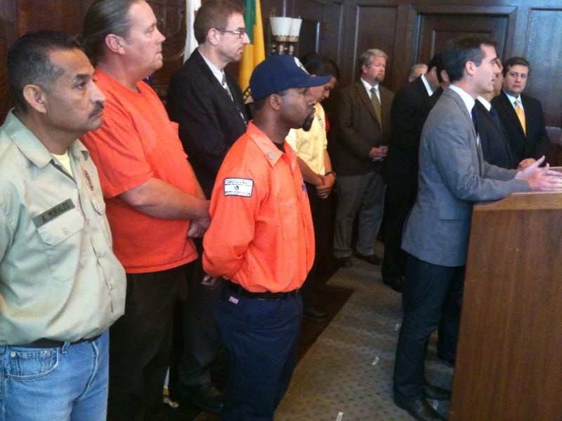 Los Angeles city workers join City Council President Eric Garcetti (at the podium) and Mayor Antonio Villaraigosa in announcing that most members of the Coalition of L.A. City Unions approved a deal to avoid unpaid furlough days.  Bargaining units representing more than 6,000 workers rejected the deal, and face 42 furlough days.