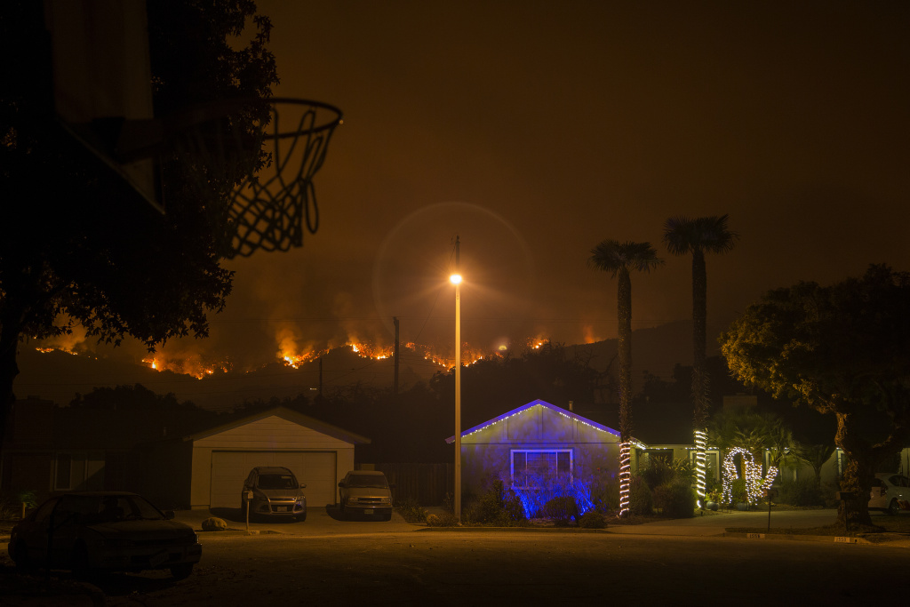 Christmas decorations illuminate a house as the growing Thomas Fire advances toward Santa Barbara County seaside communities.