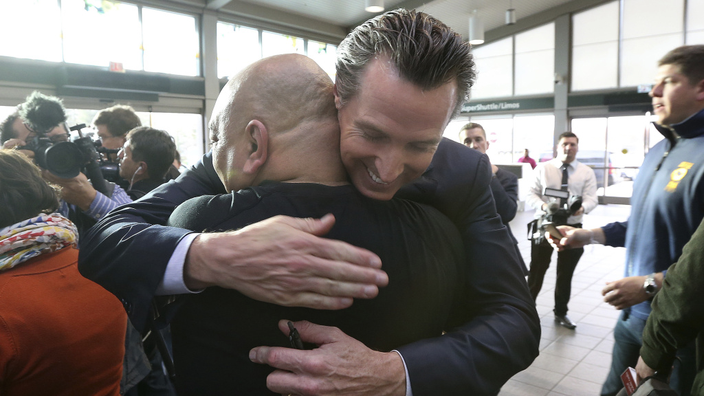California Gov. Gavin Newsom, right, hugs TSA employee Miguel Pagarigan at the Sacramento International Airport Thursday.