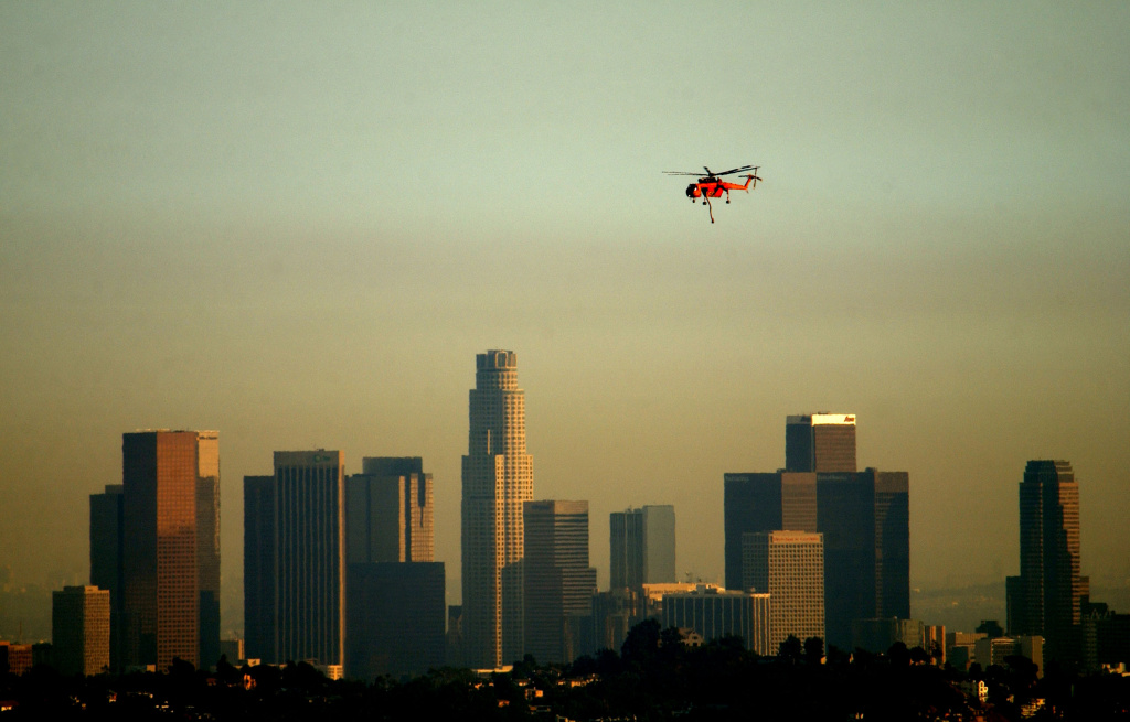 An Erickson Aircrane firefighting helicopter flies past a slightly smokey downtown Los Angeles skyline as it returns from picking water at an inner-city lake while fighting a wildfire in Glendale, California.
