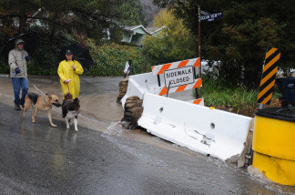 Residents walk past barriers setup to divert floodwaters as heavy rain raises the possibility of flooding and landslides due to the denuded hillside vegetation from the recent Station Fire in the La Canada Flintridge area of Los Angeles. File photo.