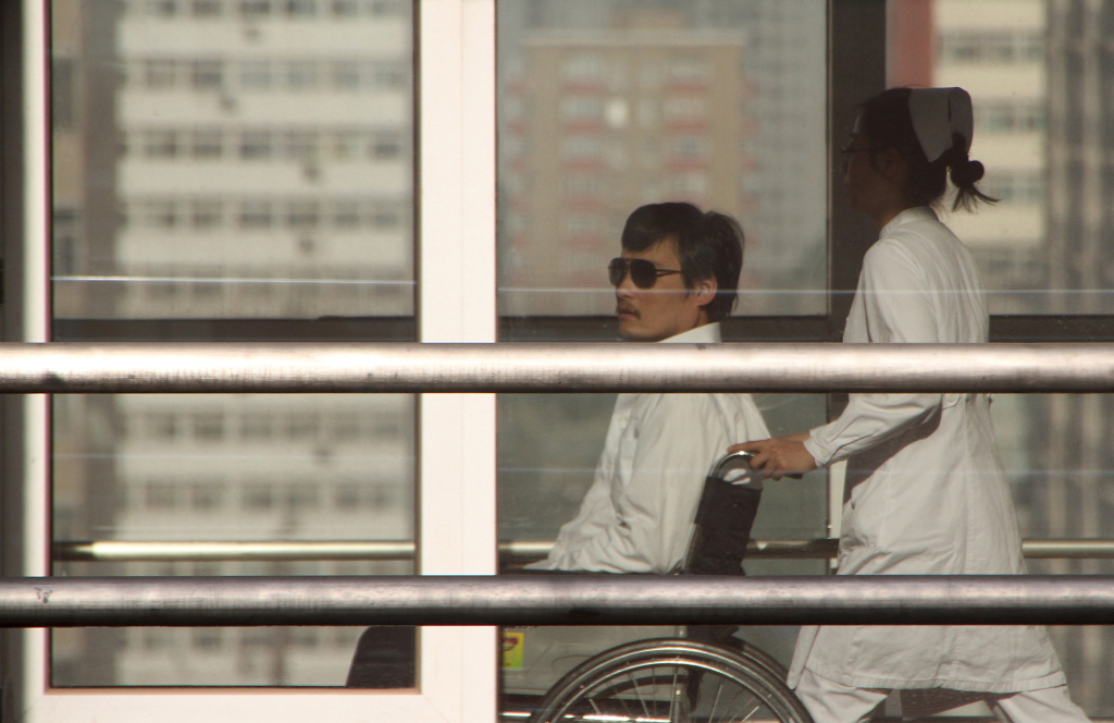 Chinese activist activist Chen Guangcheng (L) is seen in a wheelchair pushed by a nurse at the Chaoyang hospital in Beijing on May 2, 2012.