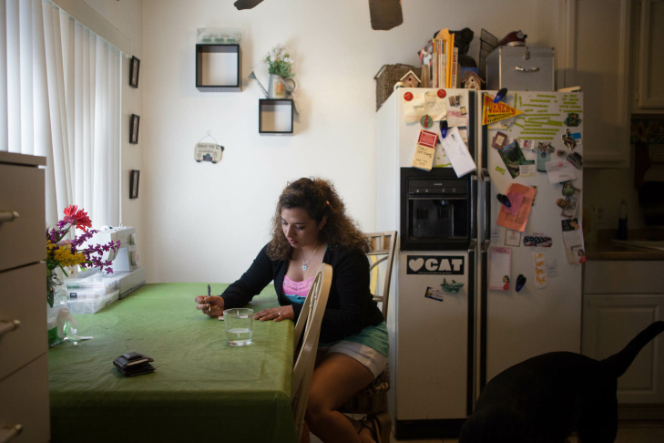 Desiree Escarcida works in her kitchen at her Buena Park apartment. She served in the Marine Corps and now attends school at Fullerton College.