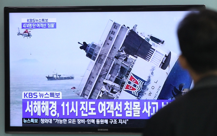 A man watches a TV news program showing a sinking passenger ship, at Seoul Railway Station in Seoul, South Korea, Wednesday, April 16, 2014. The South Korean passenger ship carrying more than 470 people, including many high school students, is sinking off the country's southern coast Wednesday after sending a distress call, officials said. There are no immediate reports of causalities. The letters on the screen read
