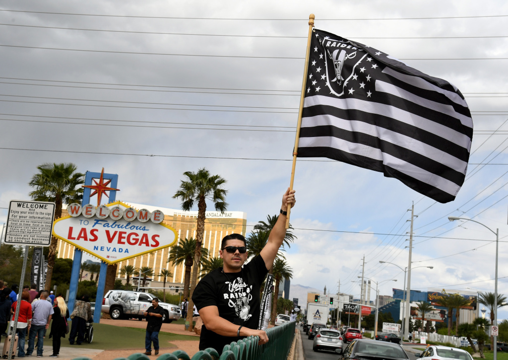 Oakland Raiders fan Matt Gutierrez of Nevada waves a Raiders flag in front of the Welcome to Fabulous Las Vegas sign.