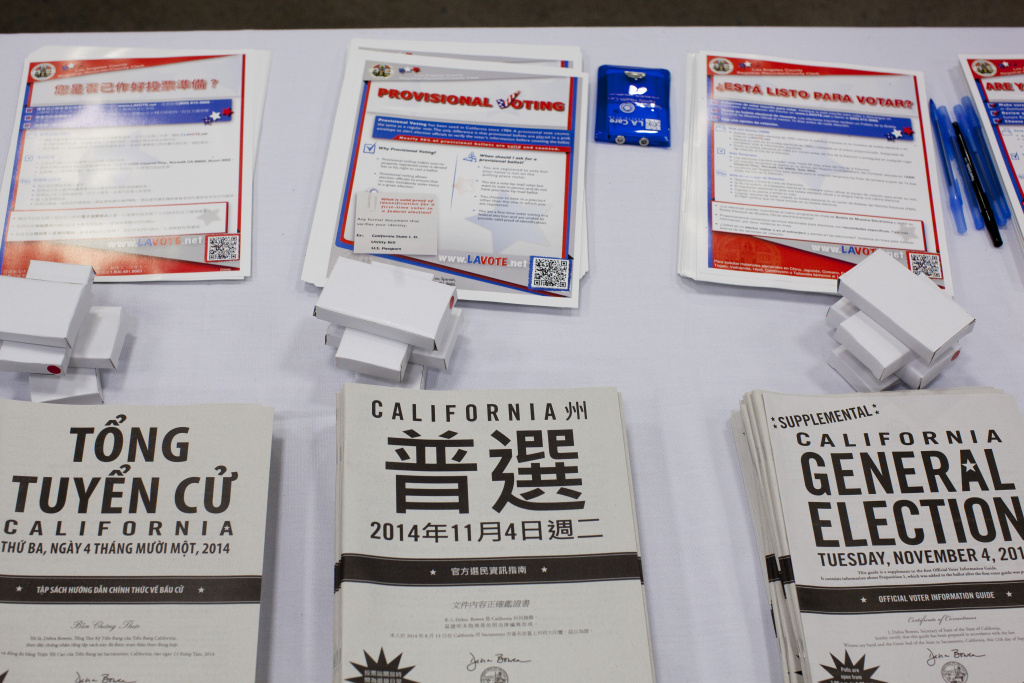 Voter registration and sample pamphlets in multiple languages, made available after a recent U.S. citizenship ceremony at the L.A. Convention Center. A new report suggests civic engagement among Asian Americans, the nation's fastest growing racial group, is steadily improving. But younger Asian American voters and those who are immigrants still lag behind.