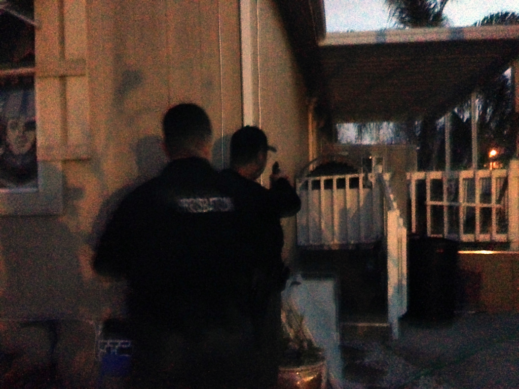 Deputy probation officers watch the back door of a house while hunting for a fugitive.