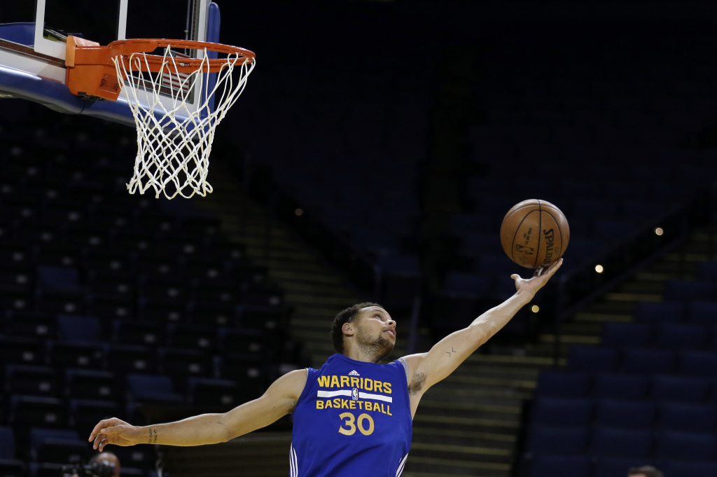 Golden State Warriors' Stephen Curry reaches for the ball during NBA basketball practice, Wednesday, June 3, 2015, in Oakland, Calif. The Warriors host the Cleveland Cavaliers in Game 1 of the NBA Finals on Thursday. (AP Photo/Ben Margot)