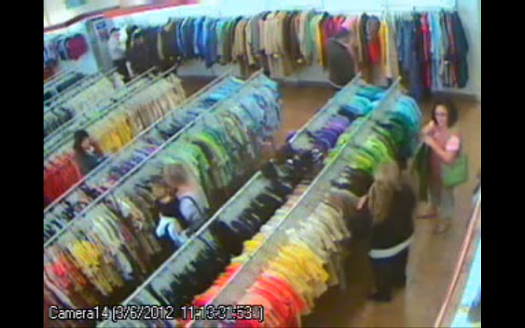 A screenshot from a Goodwill surveillance camera. The woman with brown hair is one of the suspected robbers.