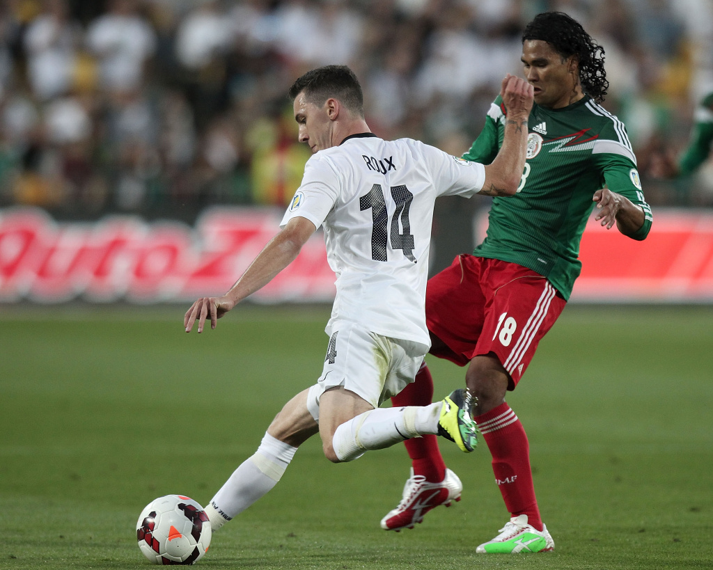 Storm Roux (L) of New Zealand is challenged by Carlos Pena of Mexico during their World Cup qualifying football match in Wellington on November 20, 2013. Mexico won 4-2.