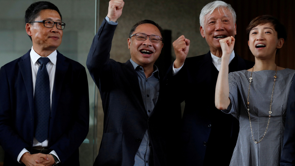 Occupy Central founders Chan Kin-man, Benny Tai and Chu Yiu-ming chant slogans with fellow democracy advocate Tanya Chan, after the four and other activists were convicted of public nuisance crimes related to Hong Kong's