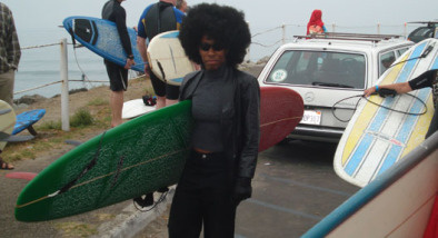 A surfer dressed as Angela Davis prepares for Doo Dah Surf.