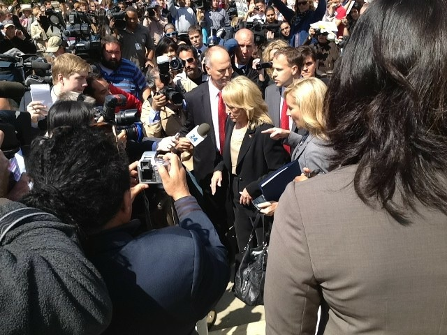 Media and protesters swarm Arizona Governor Jan Brewer as she exits U.S. Supreme Court.