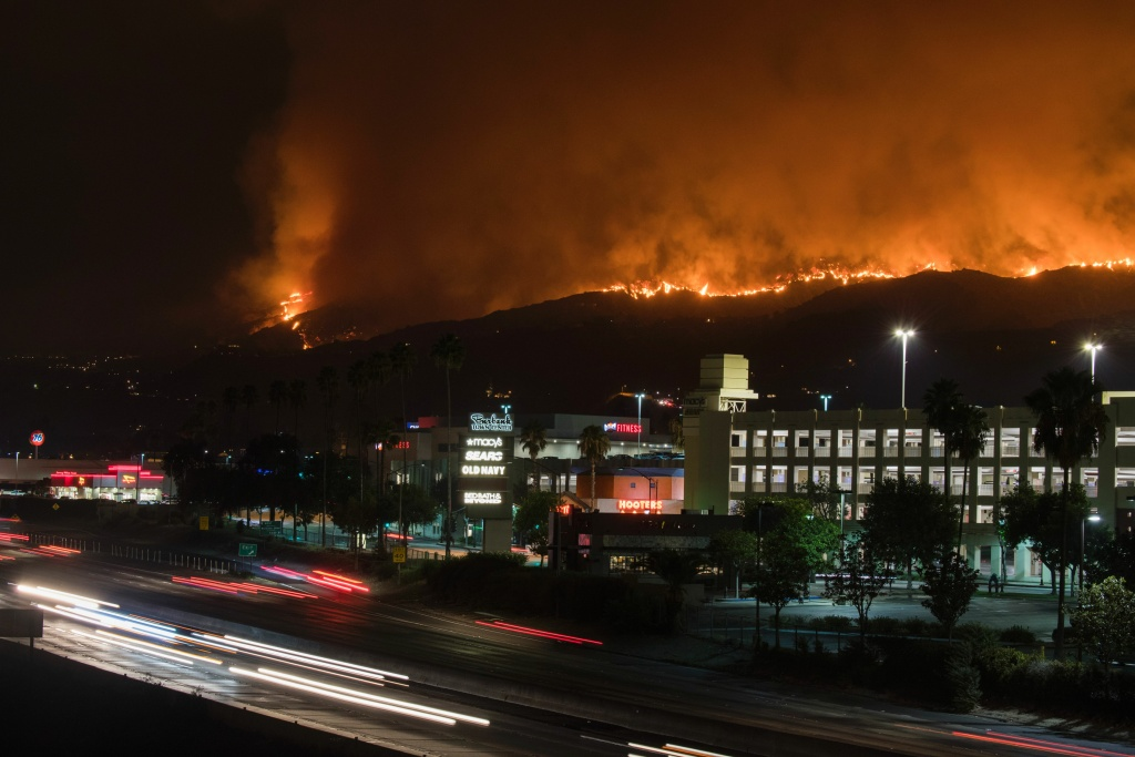 The La Tuna Canyon fire burns in the hills above Burbank, California, early September 2, 2017.  The brush fire which quickly burned 2,000 acres started on September 1 and was being driven by heat wave temperatures and high winds.   / AFP PHOTO / Robyn Beck        (Photo credit should read ROBYN BECK/AFP/Getty Images)