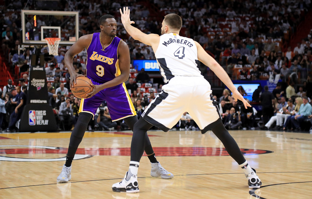 MIAMI, FL - DECEMBER 22: Luol Deng #9 of the Los Angeles Lakers passes around Josh McRoberts #4 of the Miami Heat during a game  at American Airlines Arena on December 22, 2016 in Miami, Florida. NOTE TO USER: User expressly acknowledges and agrees that, by downloading and or using this photograph, User is consenting to the terms and conditions of the Getty Images License Agreement.  (Photo by Mike Ehrmann/Getty Images)