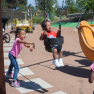 Twins Zoe and Zora McLucas, 4, push Roya Cole, 1 in a swing at the the newly completed Serenity Park in Watts, Calif.  on Monday, April 6, 2015.