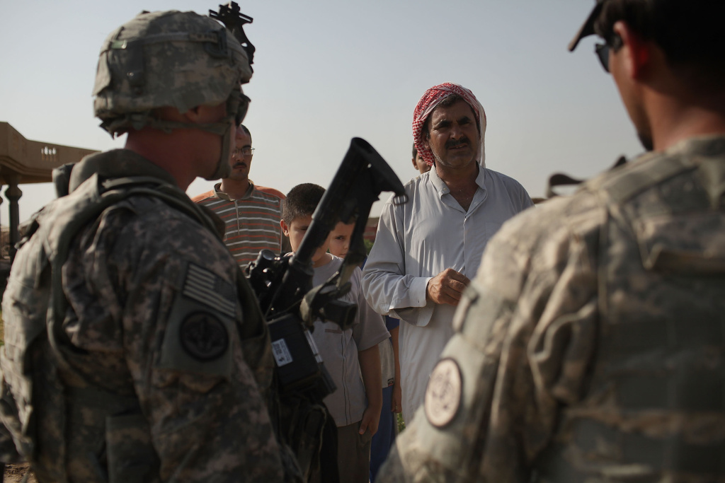 Soldiers and an Iraqi translator with the 3rd Armored Cavalry Regiment speak with a local Iraqi while on  a patrol on July 13, 2011 in Iskandariya, Iraq.