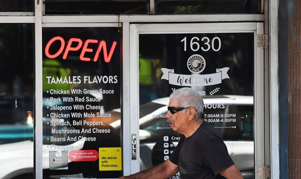 A man walks past a restaurant with an illuminated Open sign on May 5, 2021 in Los Angeles, California. - Los Angeles County is now eligible to move into the yellow Covid-19 tier in California's coronavirus reopening framework - the least restrictive tier - allowing for a gradual return to higher capacity at most businesses.