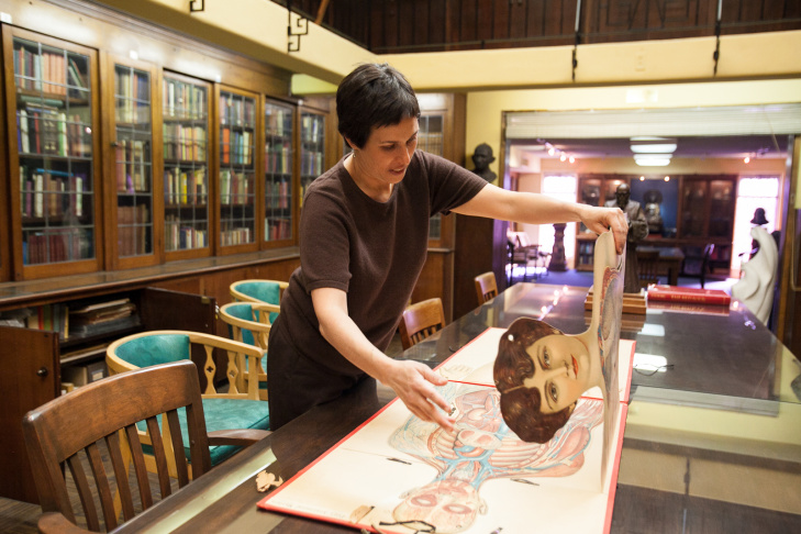Philosophical Research Society Librarian, Edie Shapiro, opens a copy of