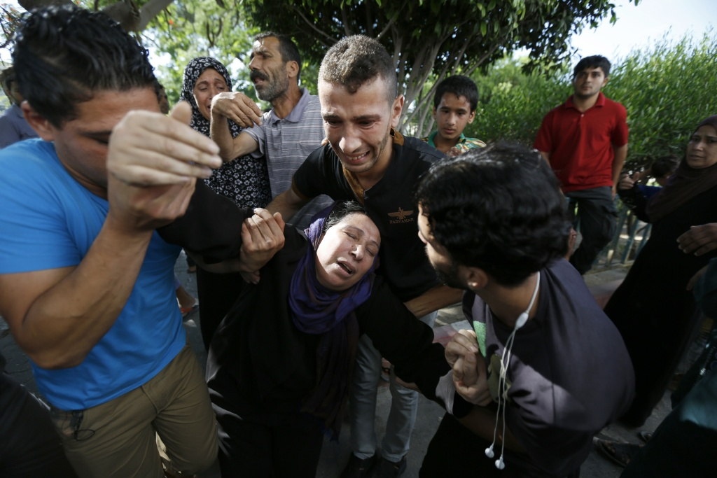 The mother of one of the four boys, all from the Bakr family, killed during Israeli shelling, collapses outside the al-Shifa hospital in Gaza City, on July 16, 2014.