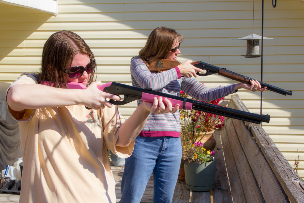 Two young women shoot BB guns. Should all imitation guns look less realistic?