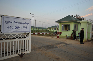 Myanmar policemen stand guard outside a compound of official guest houses where Members of Parliament stay for the duration of the opening sesion of the national parliament in the capital Naypyidaw on January 31, 2010.