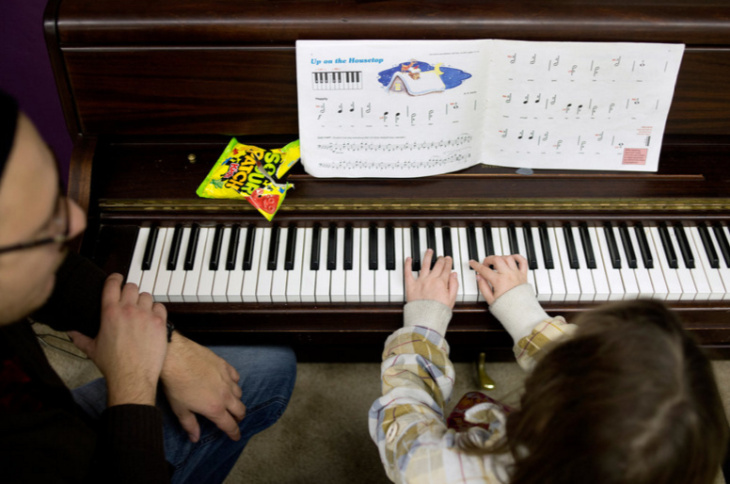 Nikia Cliff II, 6, throws paper airplanes with his Major Chords for Minors piano instructor Bruce Leaman after Cliff's lesson.