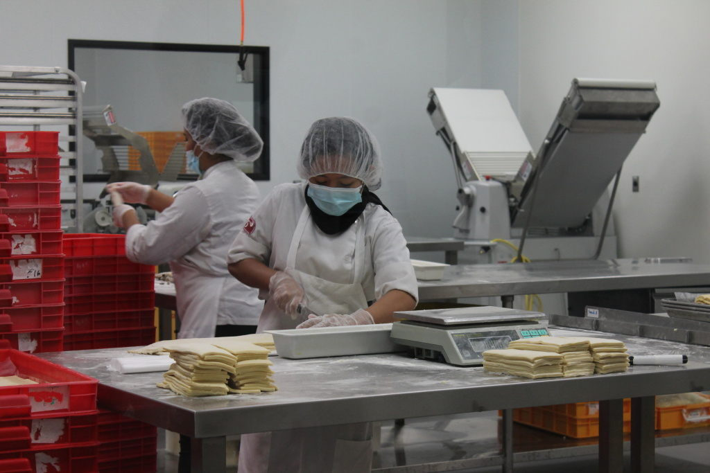 At 85°C's Central Kitchen in Brea, a worker prepares the dough for danishes.