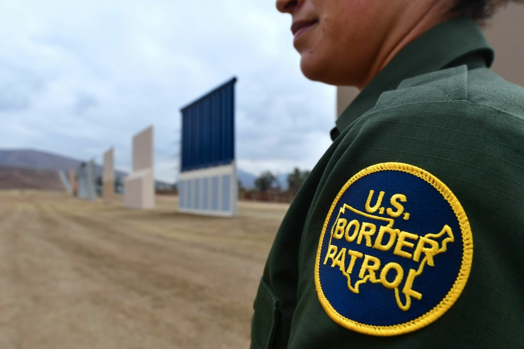 File: A U.S. Border Patrol officer stands near prototypes of President Trump's proposed border wall in San Diego.