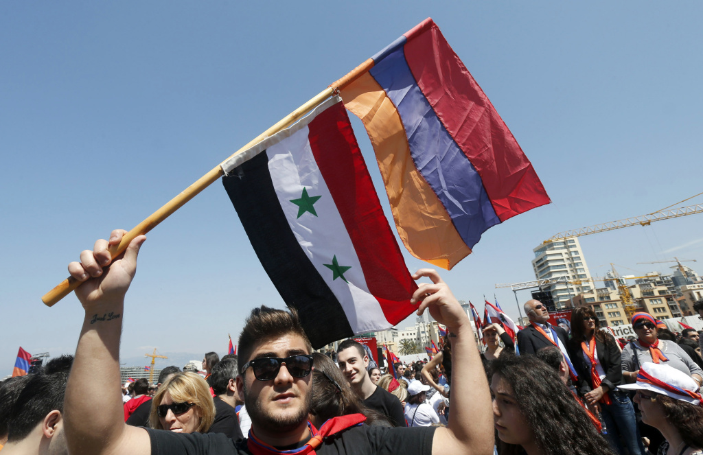 An Armenian man waves his national flag along with the Syrian national flag during a march north of the Lebanese capital Beirut, to commemorate the 98th anniversary of the Ottoman Turkish genocide against the Armenian people on April 24, 2013.