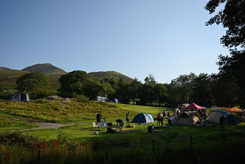 Campers wake in the early morning in the camp site beside Buttermere Lake in the Lake District in north west England on August 14, 2020, as many people take advantage of the seasonal weather to holiday at home rather than take the risk of having to self-isolate for two weeks on return from a foreign holiday.