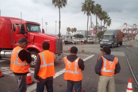 Teamsters supporters watch trucks pass at the Long Beach Container Terminal in the Port of Long Beach.