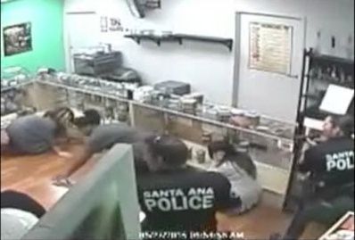 File: Screenshot showing Santa Ana police officers engaging in questionable behavior during a police raid at Sky High Holistic dispensary where the video was recorded in 2015.