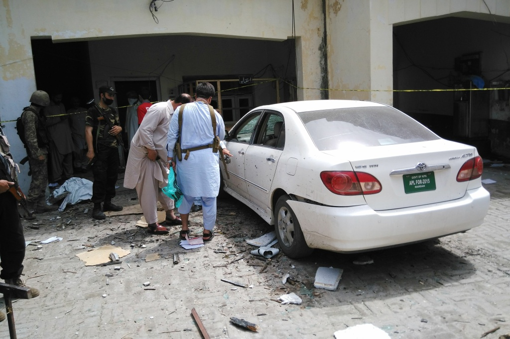 Pakistani security officials inspect the site of a suicide bomb attack on a government building in Mardan, about 50 kilometers northeast of the region's main city of Peshawar, on April 19, 2016.