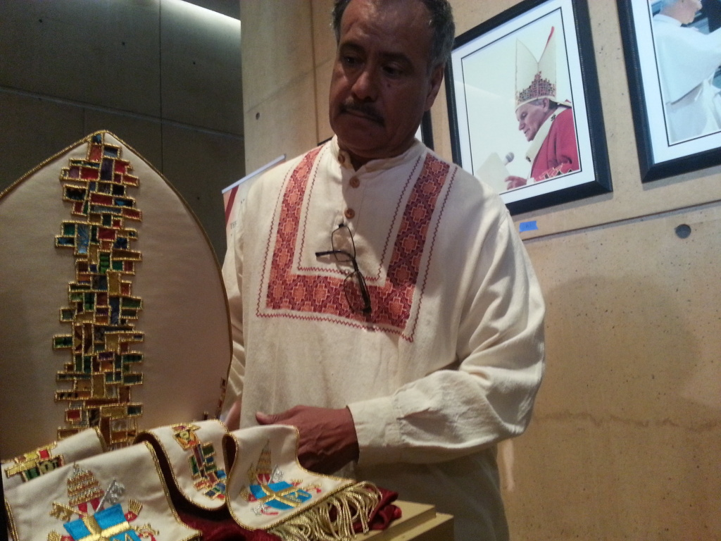 Artist Lalo Garcia designed the vestments worn by Pope John Paul II on his 1987 visit to Los Angeles. They are now on permanent display at the Cathedral of Our Lady of the Angels in downtown Los Angeles. In the background you can see pictures of Pope John Paul II wearing the items while speaking at Dodger stadium.