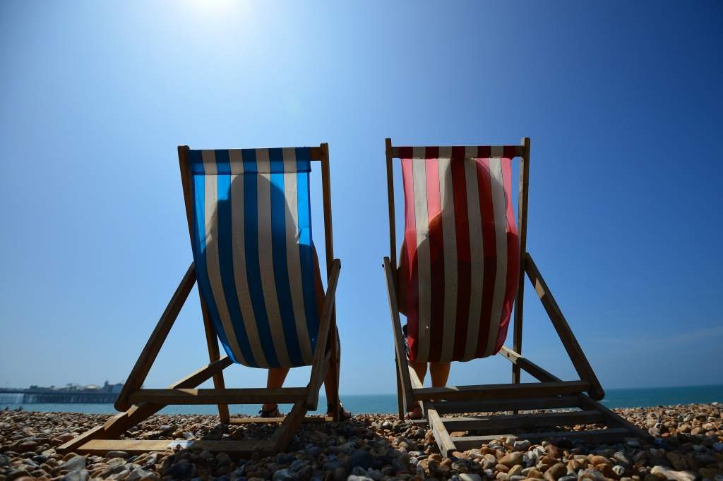 File: People relax in deck chairs on the beach in Brighton on July 18, 2014.