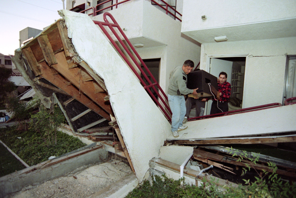 File: With help from a friend, Tigran Daniyelyan (L) carries his television from his apartment complex that was destroyed by the Northridge earthquake on Jan. 17, 1994.
