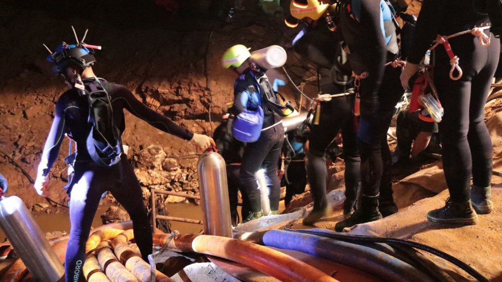 In this undated photo released by Royal Thai Navy on Saturday, July 7, 2018, Thai rescue team members walk inside the cave where 12 boys and their soccer coach are trapped. The rescue began Sunday.