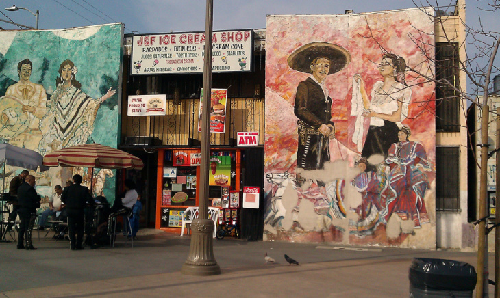 """Los Angeles City councilman Jose Huizar leans against """"History of Highland Park"""" in Boyle Heights, a privately funded mural displayed on public property."""