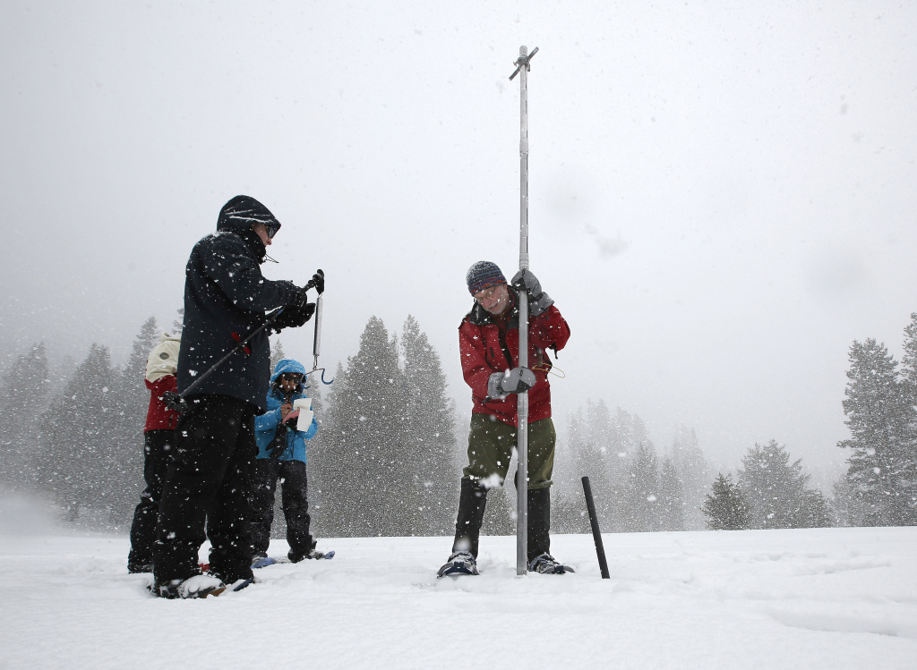 In this March 30, 2017, photo, Frank Gehrke, right, chief of the California Cooperative Snow Surveys Program for the Department of Water Resources, lifts a survey tube out of the snowpack during the manual snow survey at Phillips Station near Echo Summit, Calif.