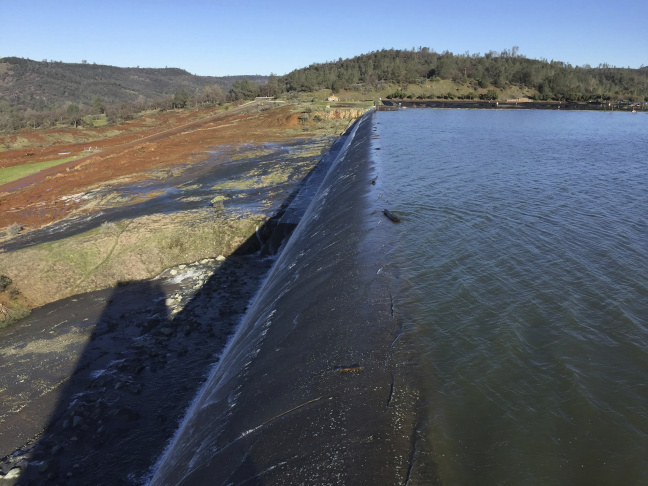 In this Feb. 11, 2017, photo released by the California Department of Water Resources, water flows over an emergency spillway at the Oroville Dam at Lake Oroville in Oroville, Calif. Water will continue to flow over the emergency spillway at the nation's tallest dam for another day or so, officials said Sunday. (Albert Madrid/California Department of Water Resources via AP)