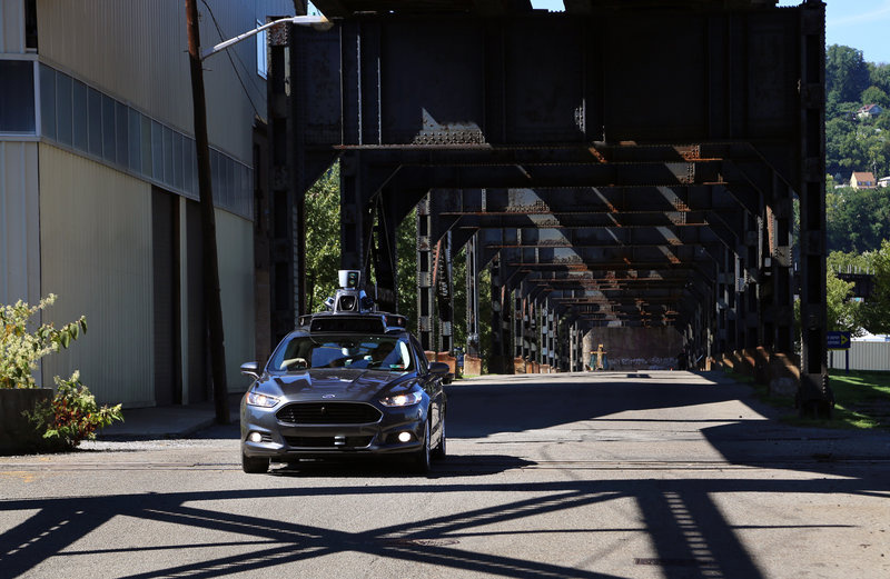 A self-driving car leaves Uber's newest riverside hub in Pittsburgh. Company officials say the Rust Belt city is perfect for beta testing, citing diverse topography, frequent weather maladies, near-constant construction and hundreds of bridges and tunnels.