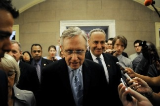 Harry Reid (D-NV) (C), followed by Senator Charles E. Schumer (D-NY) (R), tries to make his way through photographers and journalists while returning to his office.